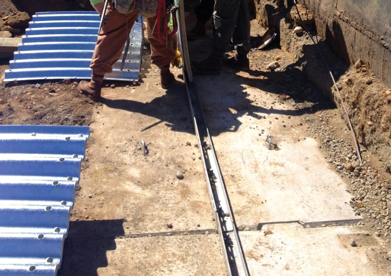 Precast concrete footing with metal base channel
